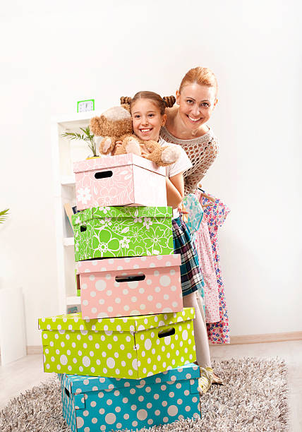 mother and daughter moving box - happy mom packing some toys stock photos and pictures