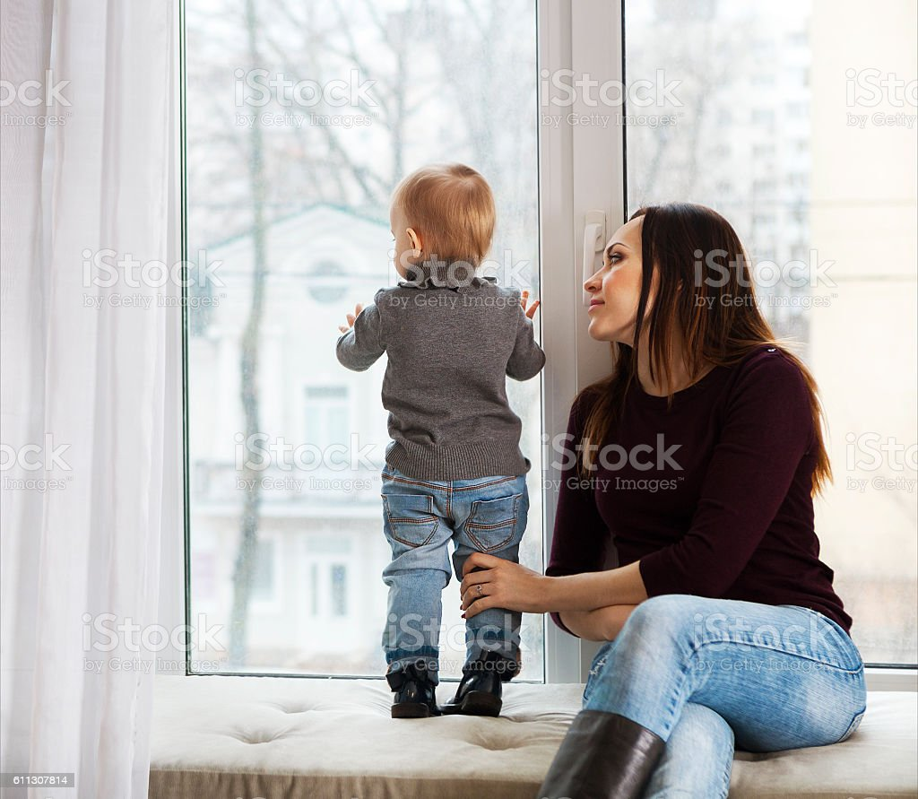 Mother and daughter near the window at home stock photo
