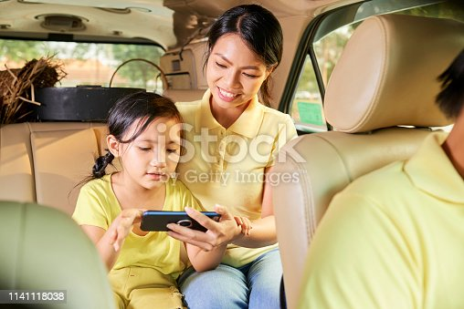 972962180 istock photo Mother and daughter on backseat with smartphone 1141118038