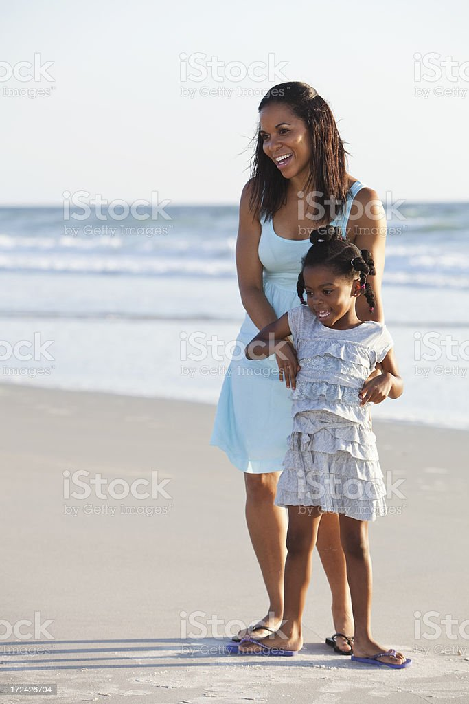Mother and daughter on beach stock photo