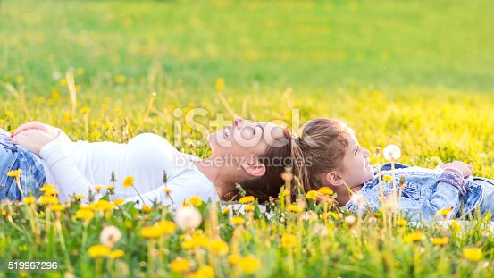 Mother and Daughter laying in grass and enjoying beautiful spring day. Their heads touching each other with bodies pointing opposite ways. Both smiling with eyes closed. Low angle view.