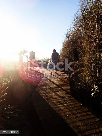 Mother and three year old daughter walking on a boardwalk in Kiawah Island, South Carolina. They appear to be entering a brightly lit supernatural area suggesting an afterlife.