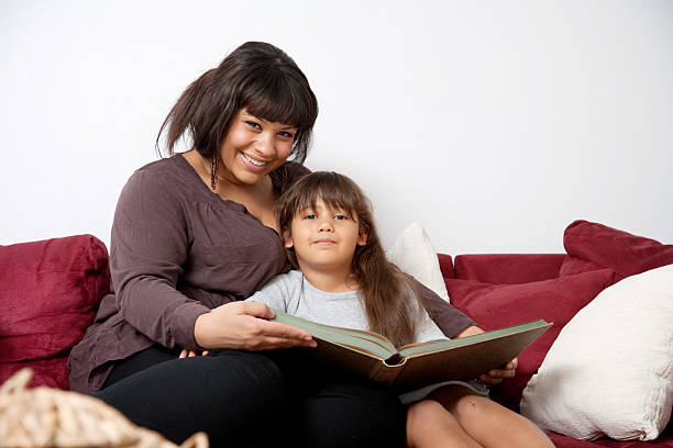 """Mother and daughter on couch reading a book """"A young woman in the city at dusk with a phone.Mother and daughter enjoying some quality time on their couch in their living room, reading a book.More:"""" haitian ethnicity stock pictures, royalty-free photos & images"""