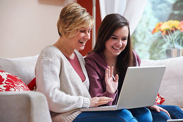 Mother and daughter on laptop stock photo