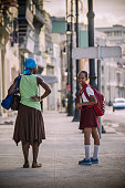Havana, Cuba - November 6, 2015: Mother and teenage daughter on the sidewalk at Malecon in Havana, Cuba. Teenager is dressed in school uniform and looking at camera. People in the background. This is a famous downtown shore line, lined up with great architecture from past now mostly run down after years being exposed to elements from Caribbean sea. Popular place for people of Havana to hang around, be in love, play music and fish. A must see location when visiting this great city. November, late afternoon in winter, people sitting on the wall near water.