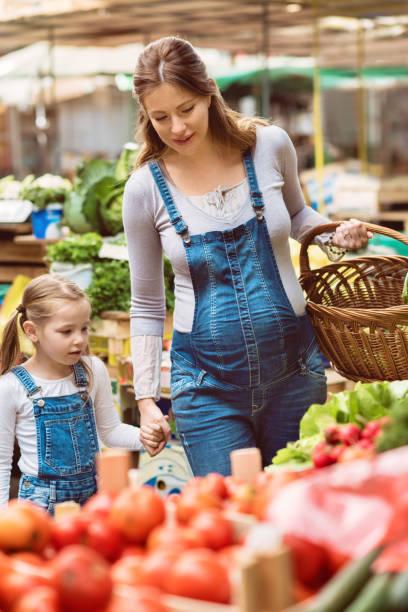 mutter und tochter auf dem bauernmarkt kaufen gesund - latzhose für schwangere stock-fotos und bilder