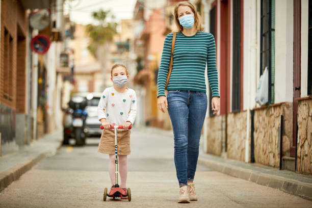 Mutter und Tochter auf der Straße tragen Gesichtsmasken für COVID-19 – Foto