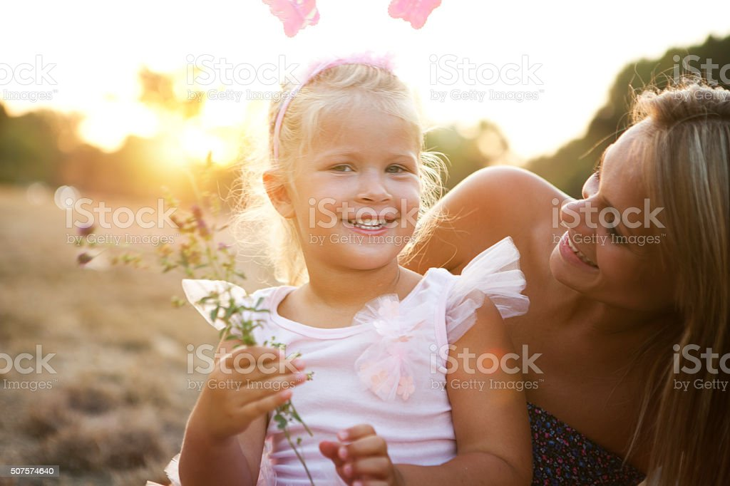 Mother and daughter outdoors in a meadow. stock photo