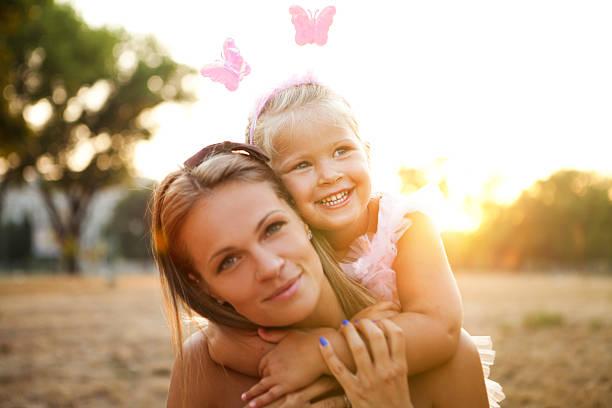mãe e filha ao ar livre em um prado. - mãe criança brincar relva efeito de refração de luz imagens e fotografias de stock