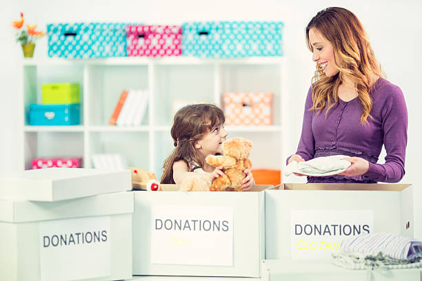 mother and daughter packing clothesand toys in donation box. - happy mom packing some toys stock photos and pictures