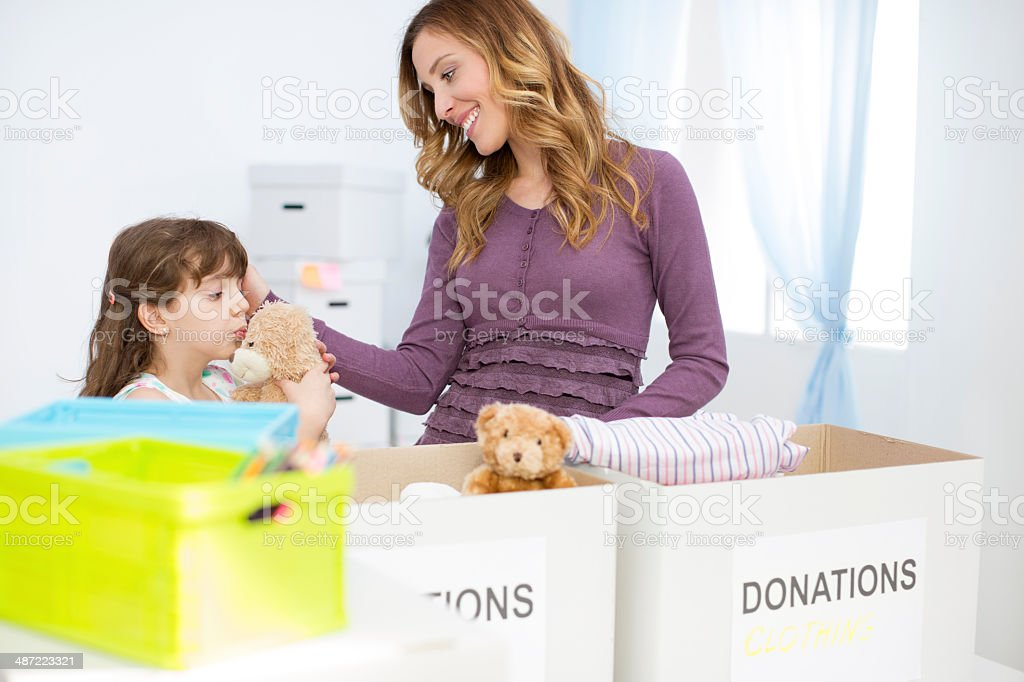 Mother and daughter packing clothesand toys in donation box. stock photo