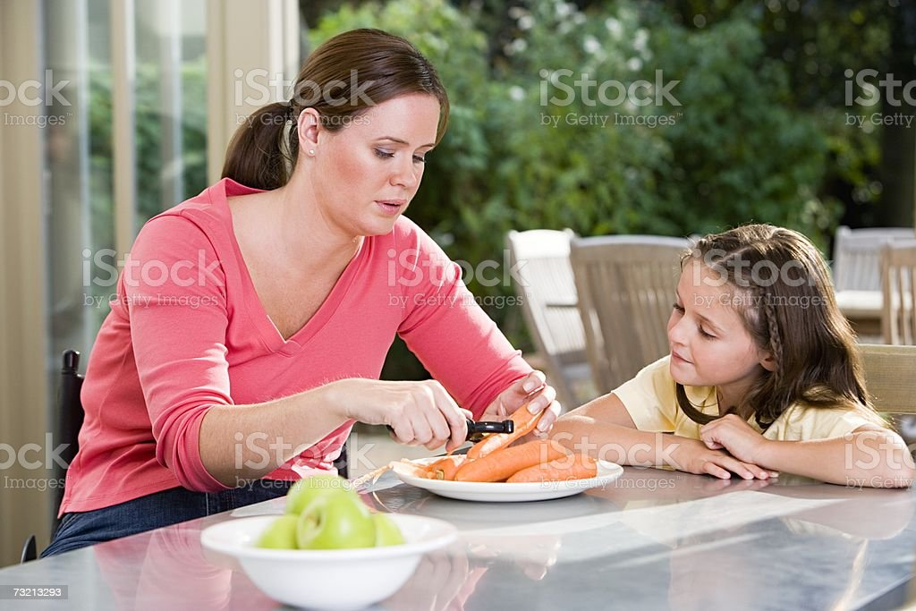 Mother and daughter peeling carrots royalty-free stock photo