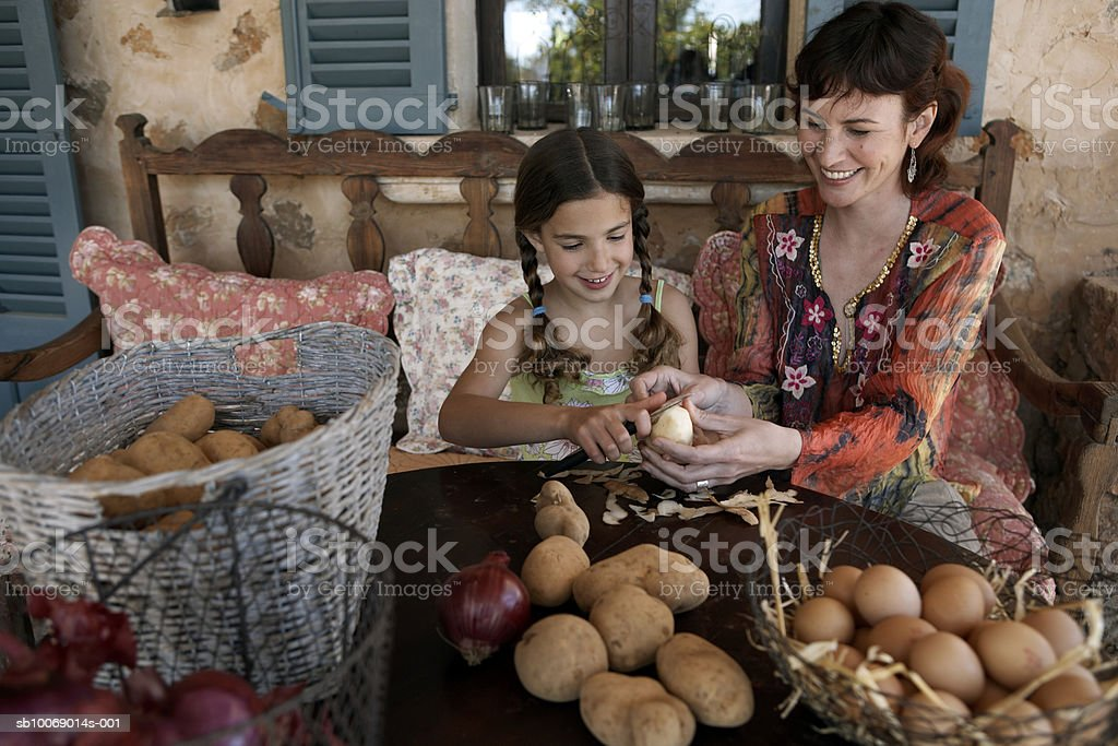 Mother and daughter (8-9) peeling potatoes on porch royalty-free stock photo