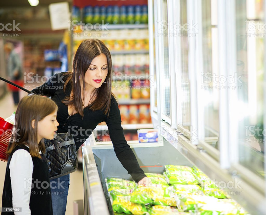 Mother and daughter pick out frozen food items stock photo