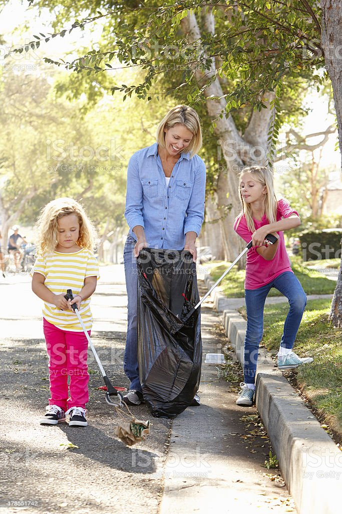 Mother And Daughter Picking Up Litter In Suburban Street royalty-free stock photo