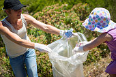 Mother and daughter picking up rubbish