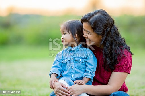 A mother and daughter are outdoors in the open. They are sitting together and smiling for the camera.