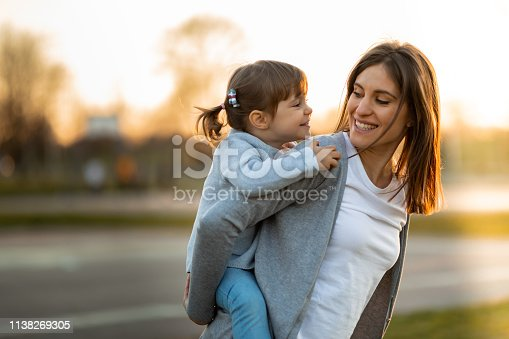 Mother and little girl having fun in piggyback ride outdoors.