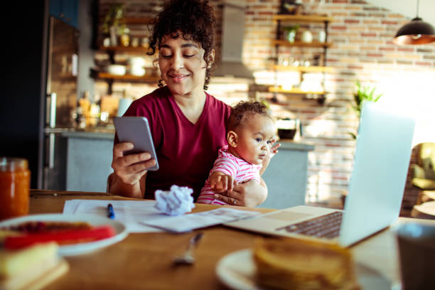 Mother and Daughter Close up of a mother using a phone with her daughter while having breakfast and doing bills messy home office stock pictures, royalty-free photos & images