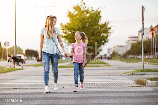 Mother is holding daughter hand and walking