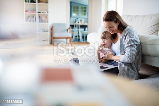 Close up of a mother and daughter using a laptop at home