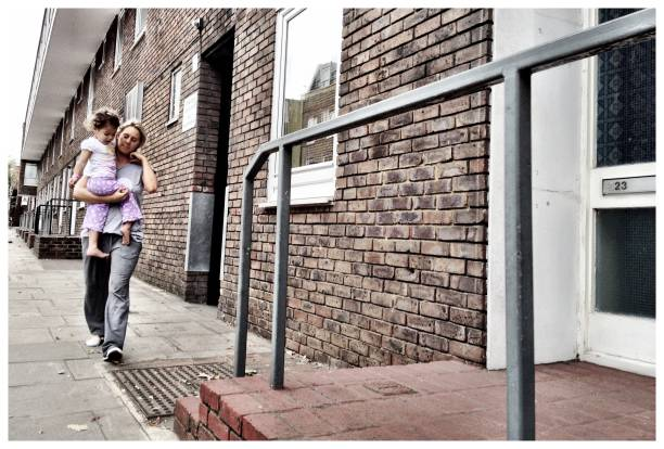 """Mother and daughter """"London, UK - 16 September 2012: A white mother carrying her mixed-race daughter along the pavement outside a block of council flats near the Holloway Road district of North London."""" desaturated stock pictures, royalty-free photos & images"""
