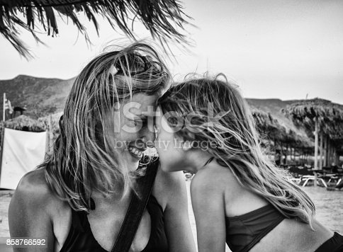 A Mother and Young Daughter Embrace on a Beach in the Greek Islands