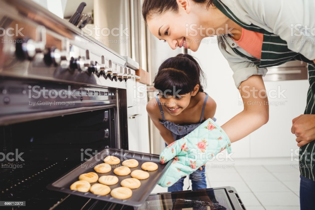 Mother and daughter placing cookies in oven stock photo