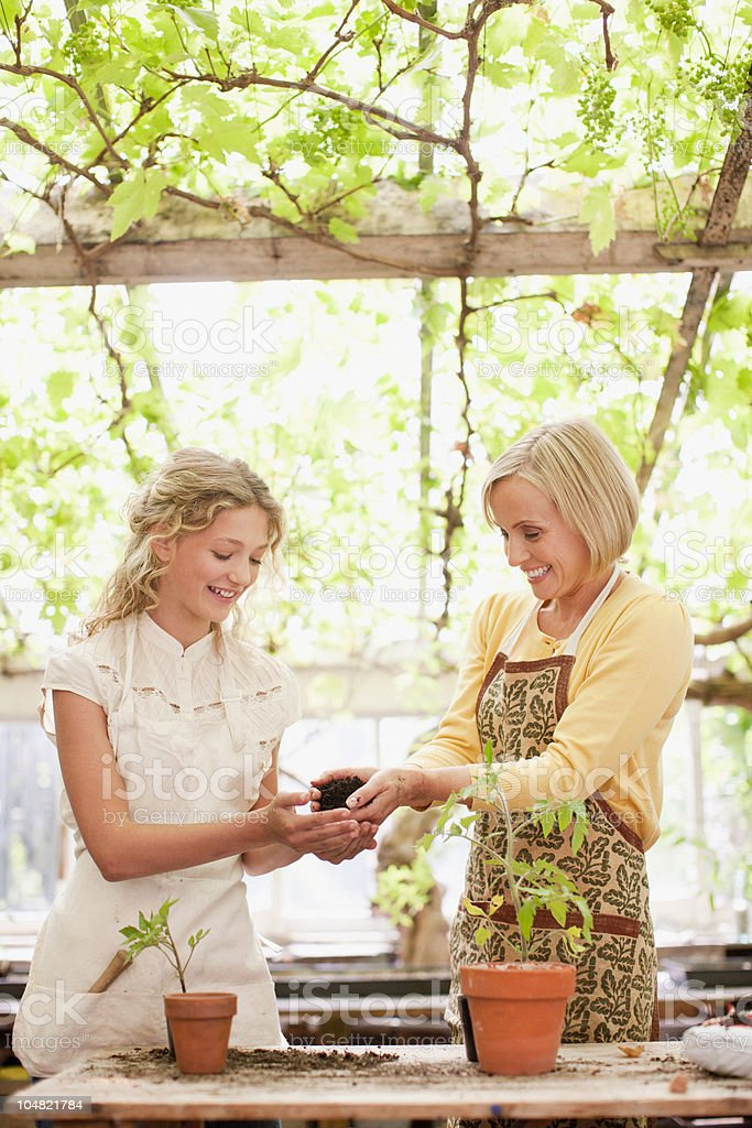 Mother and daughter planting seedlings in greenhouse royalty-free stock photo