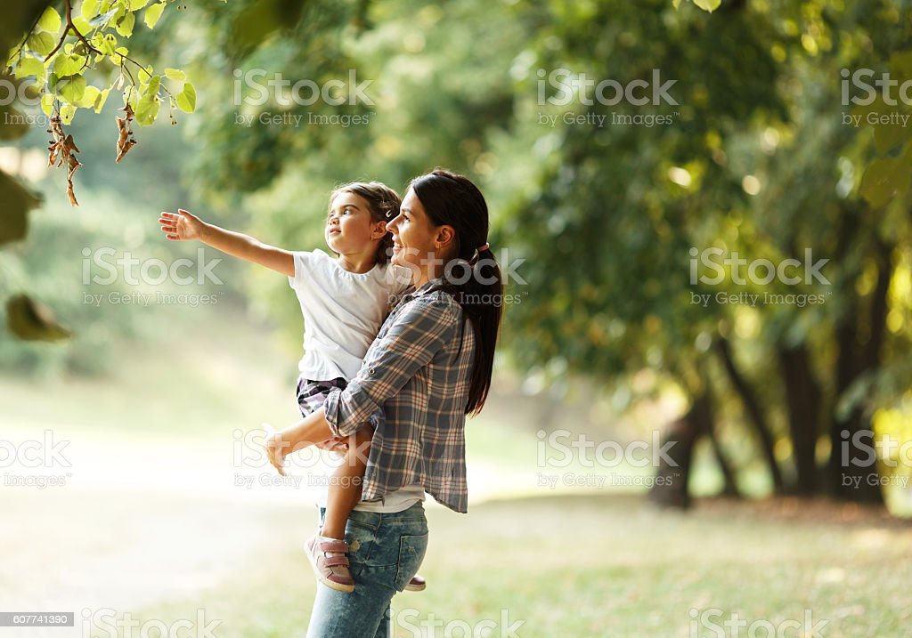 Mother and daughter playing and running around the park stock photo