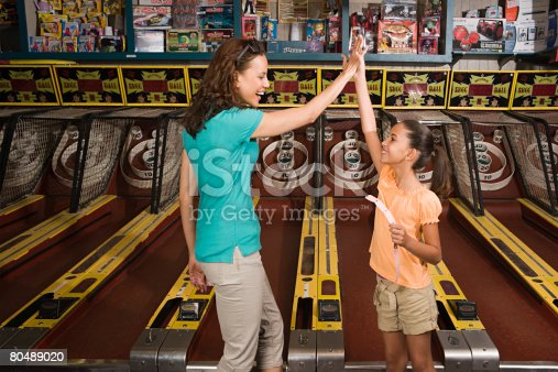 istock Mother and daughter playing arcade game 80489020