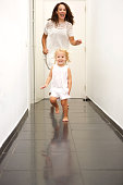 Full length portrait of cute little girl running at home with her mother in back