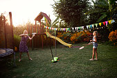 Mother and daughter playing badminton in backyard