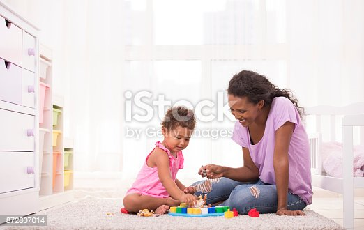 istock Mother and daughter playing educational game. 872807014