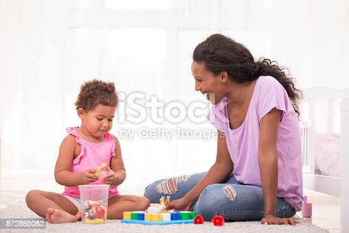 istock Mother and daughter playing educational game. 872865082