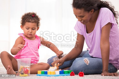istock Mother and daughter playing educational game. 872870438