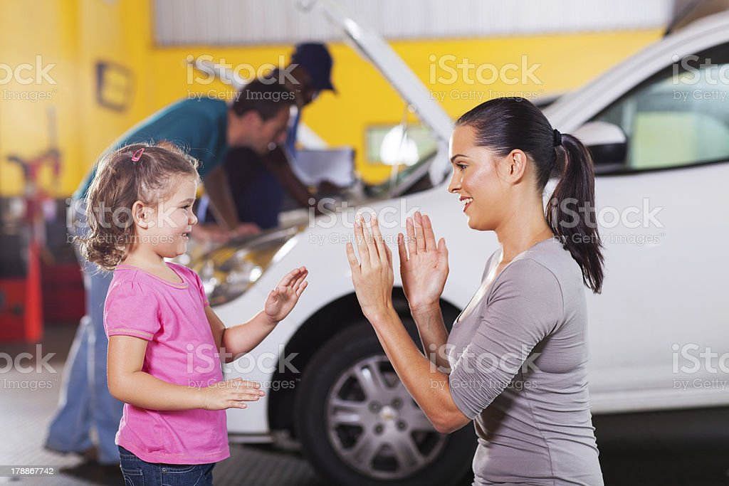 mother and daughter playing game while waiting in garage royalty-free stock photo