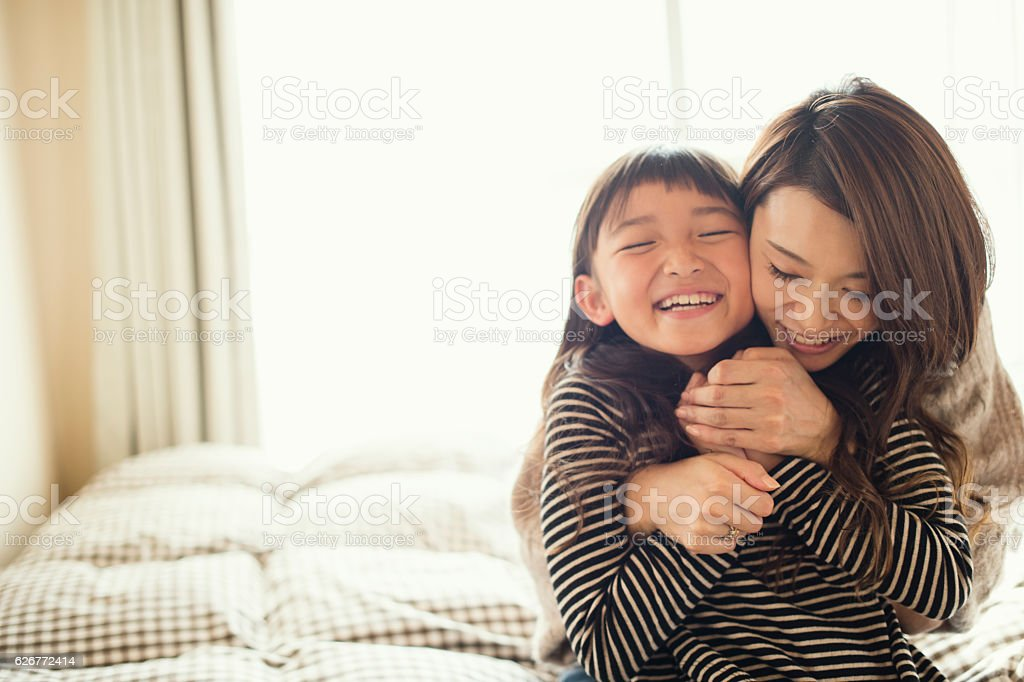 Mother and daughter playing in bed room stock photo