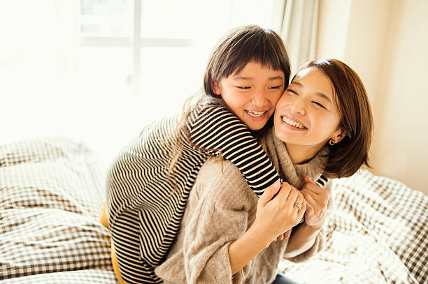 mother and daughter playing in bed room - 子供時代 ストックフォトと画像