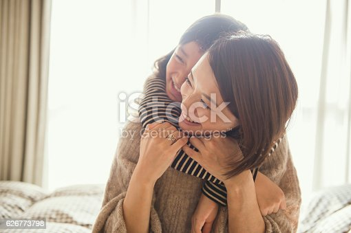 istock Mother and daughter playing in bed room 626773798