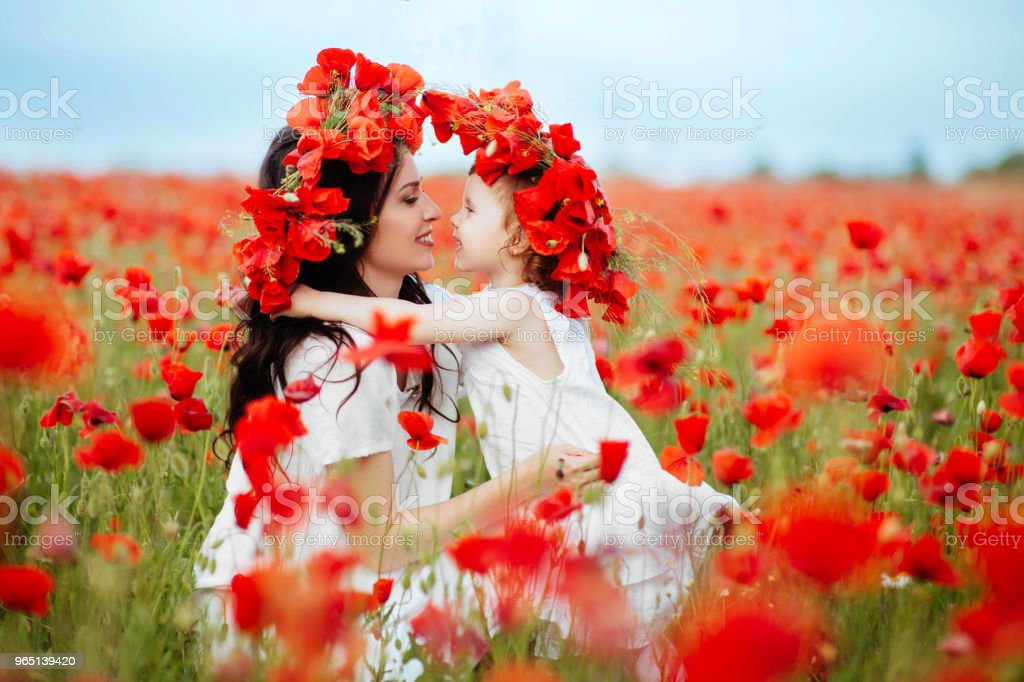 mother and daughter playing in flower field royalty-free stock photo