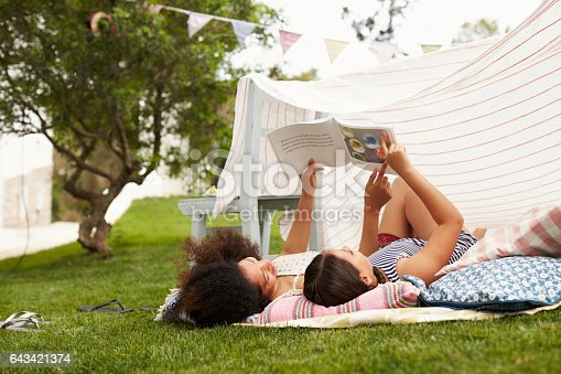 Mother And Daughter Playing In Home Made Garden Den
