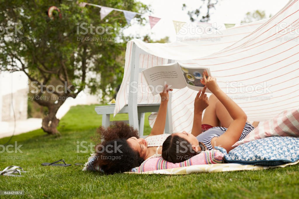 Mother And Daughter Playing In Home Made Garden Den stock photo