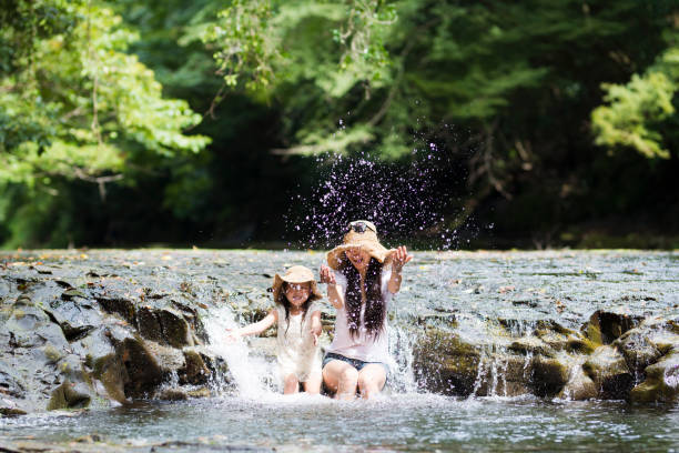mutter und tochter spielen im bergbach - kinder picknick spiele stock-fotos und bilder