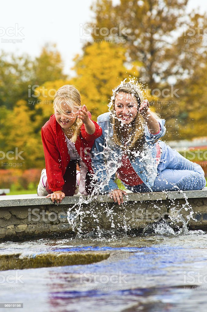 Mother and daughter Playing in Outdoor Water Fountain royalty-free stock photo