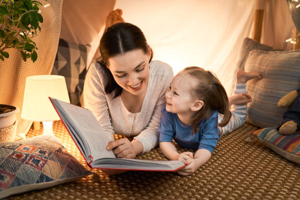 mother and daughter playing in tent stock photo