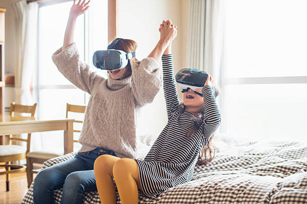 Mother and daughter playing in virtual reality glasses in bedroom ストックフォト