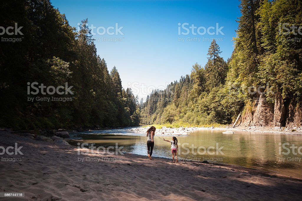 Mother and daughter playing near river in forest stock photo