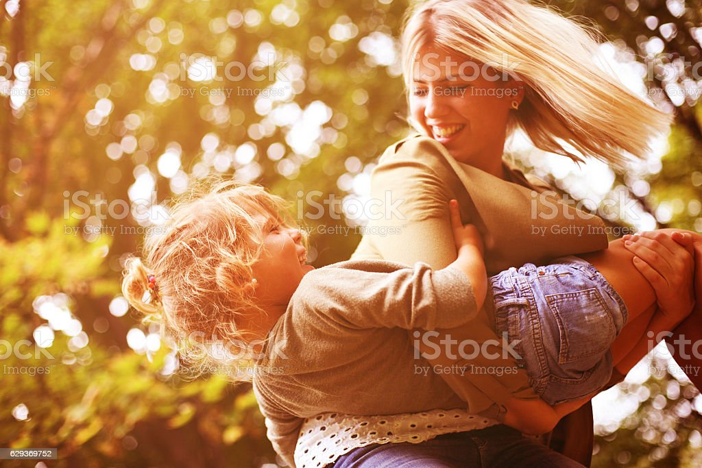 Mother and daughter playing outdoor. stock photo