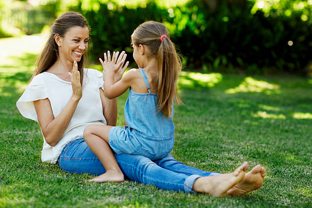 Mother and daughter playing pattycake in park – Foto